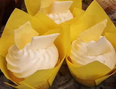 Lemon cupcakes filled with lemon curd and topped with fluffy buttercream and lemon flavored white chocolate shards
